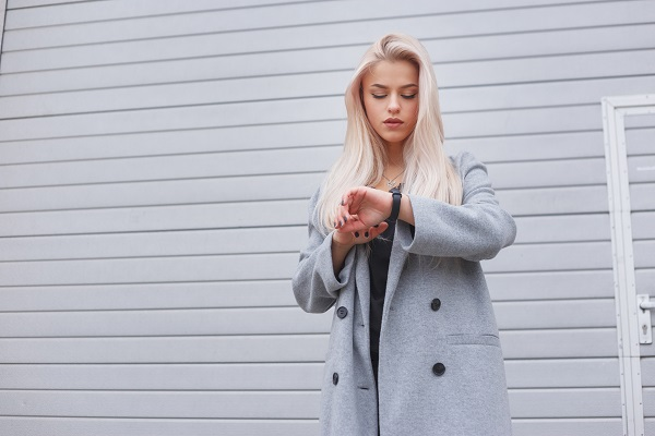 Young fashionably dressed blonde Russian girl in a coat uses a smart bracelet standing outdoors