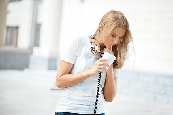 Blond-haired Russian girl walking with the headphones while sipping a beverage