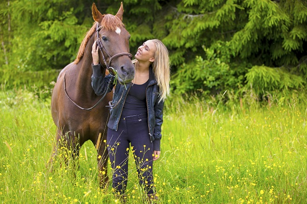 Young blonde Russian woman with her Arabian horse standing in the field