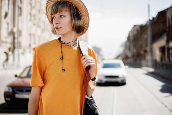 Young Russian girl with headphones in a yellow T-shirt and a straw hat walks with a backpack along a city