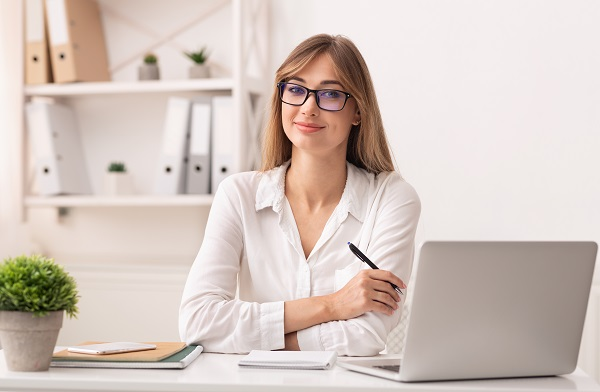 Confident entrepreneur Russian lady sitting at her laptop working in the office