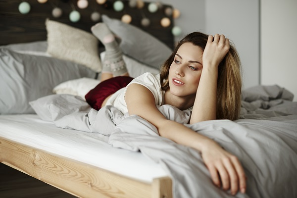 Thoughtful single charming Russian woman lying on her stomach in a bedroom
