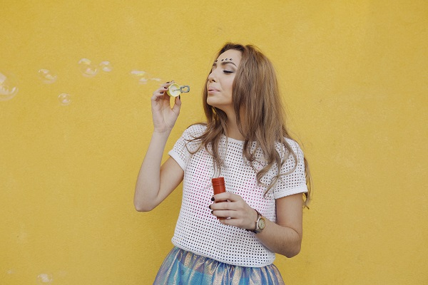 Young pretty Russian woman making soap bubbles in front of the camera while walking on the street