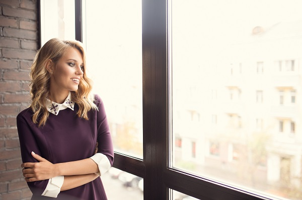 Attractive young smiling Russian woman spending her time at home near a window