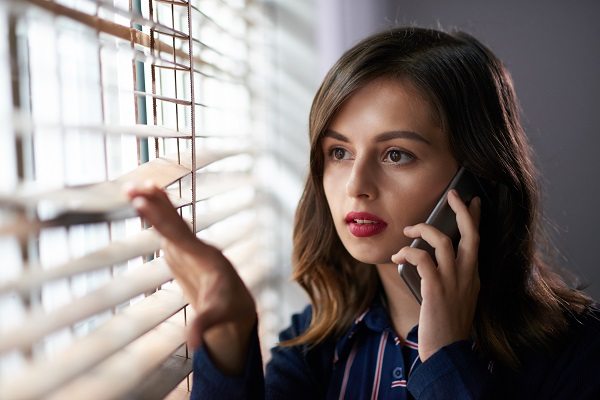 Attractive brunette Russian woman talking to a smartphone while looking out of the window