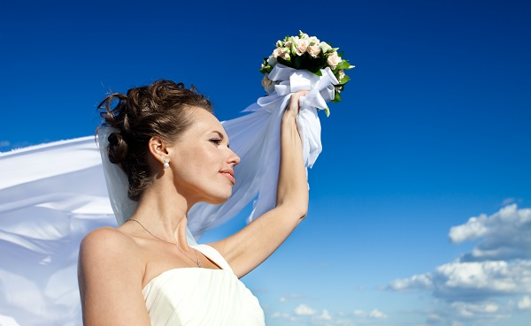 Young charming brunette Russian bride walking with a bouquet of roses in her left hand
